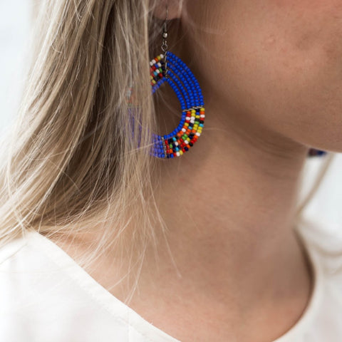 Model wearing beaded teardrop earrings made by artisans in Kenya