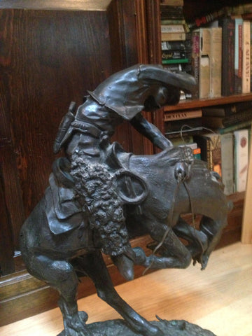 "After Frederic Remington (American, 1861- 1909), a bronze reproduction of ""Cowboy on a Bucking Bronco"""