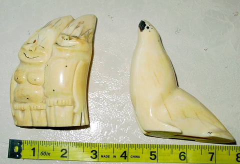 Attributed to an Inuit Alaskan Carver, Two Billikens: an Inuit Couple and a Seal, carved walrus ivory, early 20th century