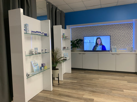 Inside store, white display cases with product and tv with video