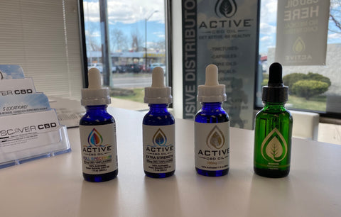 Three different types of CBD tincture sitting on a counter in the Discover CBD Store