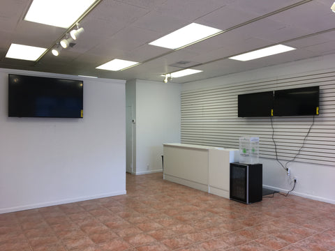Inside of store with white walls and tv screens and counter top