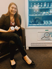 woman sitting in chair next to vending machine holding salve jars
