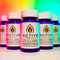 active cbd oil capsules bottles in pyramid style with multi colored background