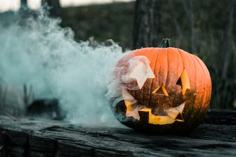 carved pumpkin with smoke near fence
