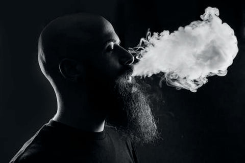 man with beard surrounded by smoke