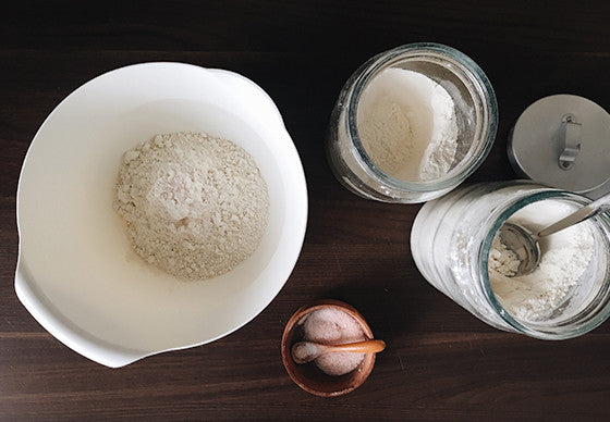 Close up of a white plastic mixing bowl with wholewheat flour, a salt cellar and a jar containing flour on a dark wooden kitchen counter