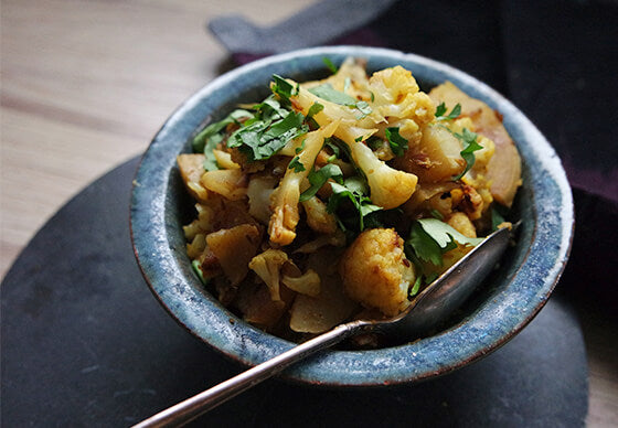 close up of aloo gobi—pan roasted-cauliflower and potatoes ina  blue ceramic bowl on a wooden kitchen counter top