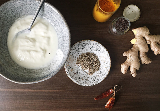 Overhead view of ingredients for an Indian dish made from yoghurt, onions, chilli and