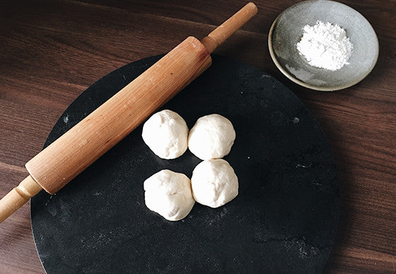 Four balls of freshly kneaded roti dough on a black slate base with a wooden rolling pin