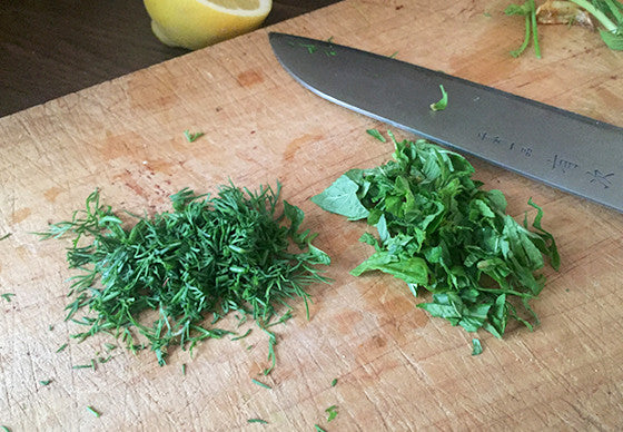 Freshly chopped dill and basil next to a knife on a wooden cutting board