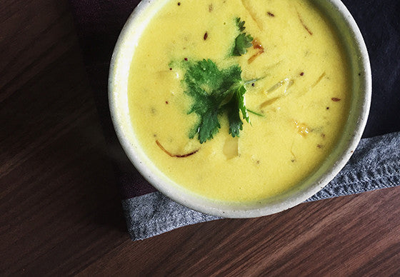 Close up of kadhi, a tangy, light curry made from yoghurt, water and chickpea flour, spiced with cumin, onions and mustard seeds served in a small ceramic bowl