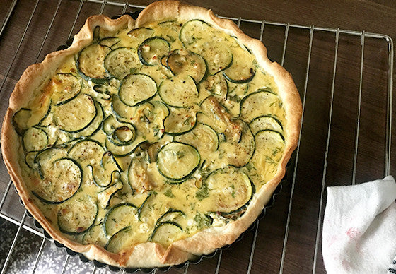 Freshly baked zucchini tarte with puff pastry resting on a wire rack, on a dark wooden kitchen counter