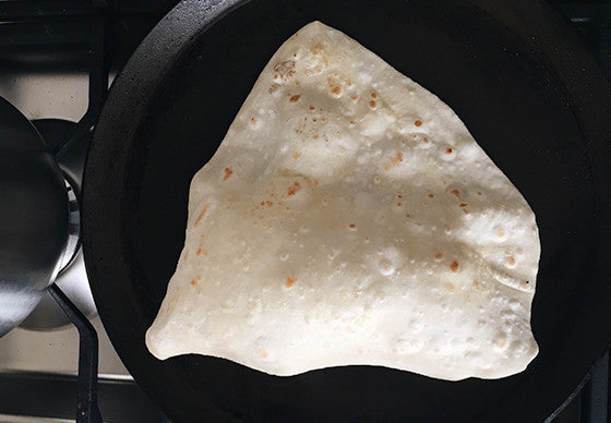 Closeup of a chapati cooking on a pan in a kitchen