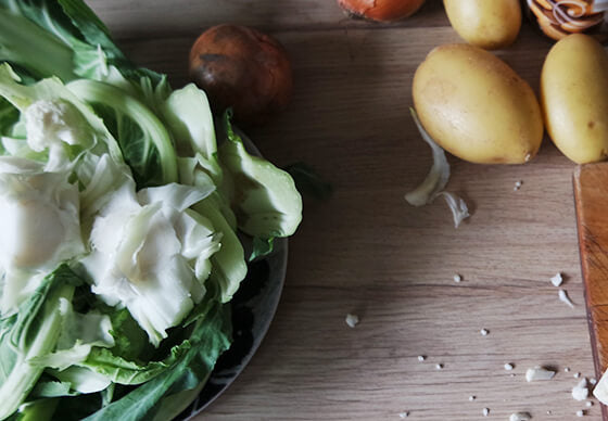 close up of cauliflower and potatoes on a wooden kitchen counter top