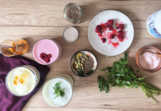 overhead shot of three glasses of lassi, a cooling yoghurt drink for summer time, with ingredients fruits, herbs and spices surrounding them