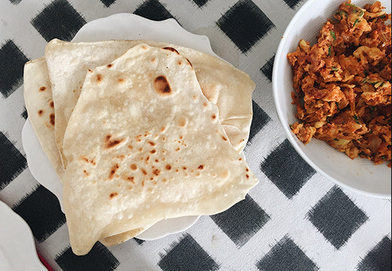 Closeup of a plate of chapatis alongside a bowl with Indian-style scrambled eggs, on a black and white checkered tablecloth