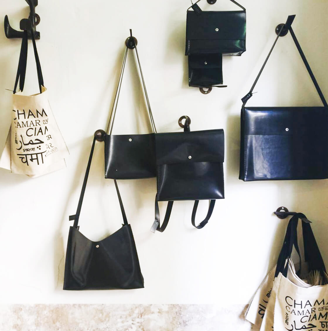 Different bags made from recycled car tyres displayed on the wall at Clarke House Collective in Mumbai, India. They are from the brand Chamar Studio by Sudheer Rajbhar