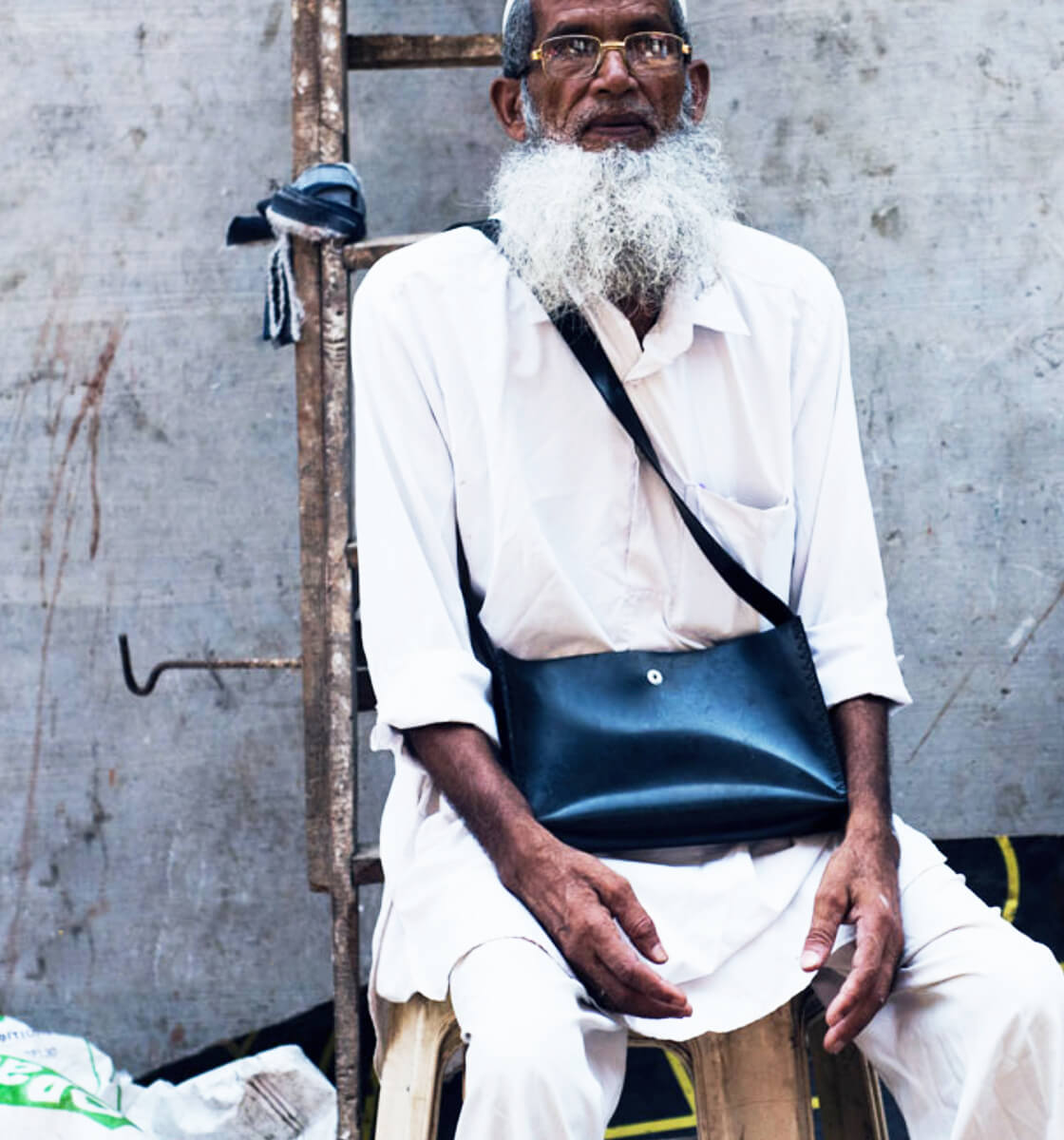 an old Muslim gentleman models a bag from Chamar Studio's Bombay Black collection in Mumbai India