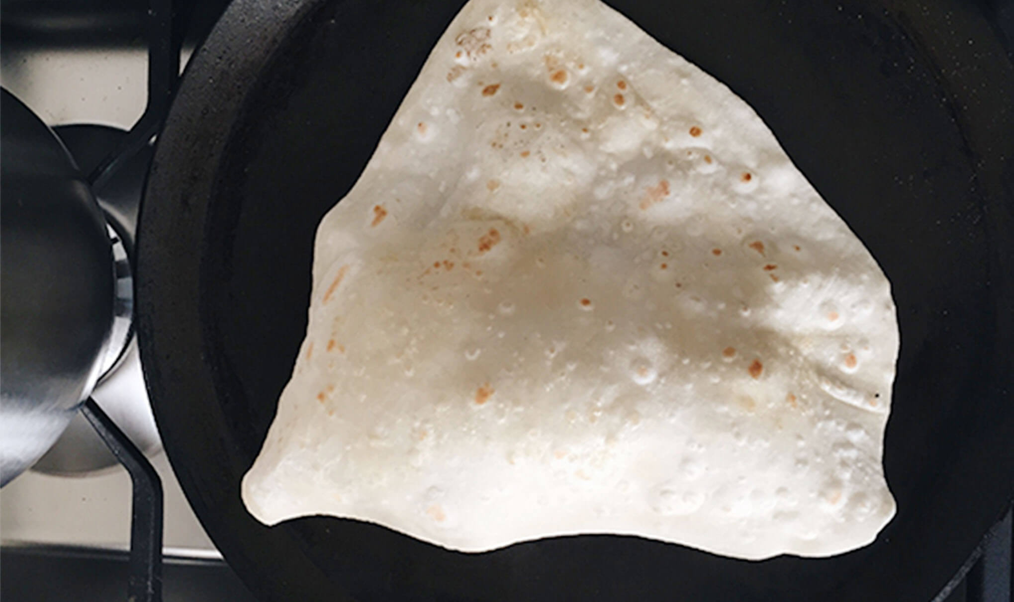 Chapati made from wholewheat flour cooking on a dark flat pan