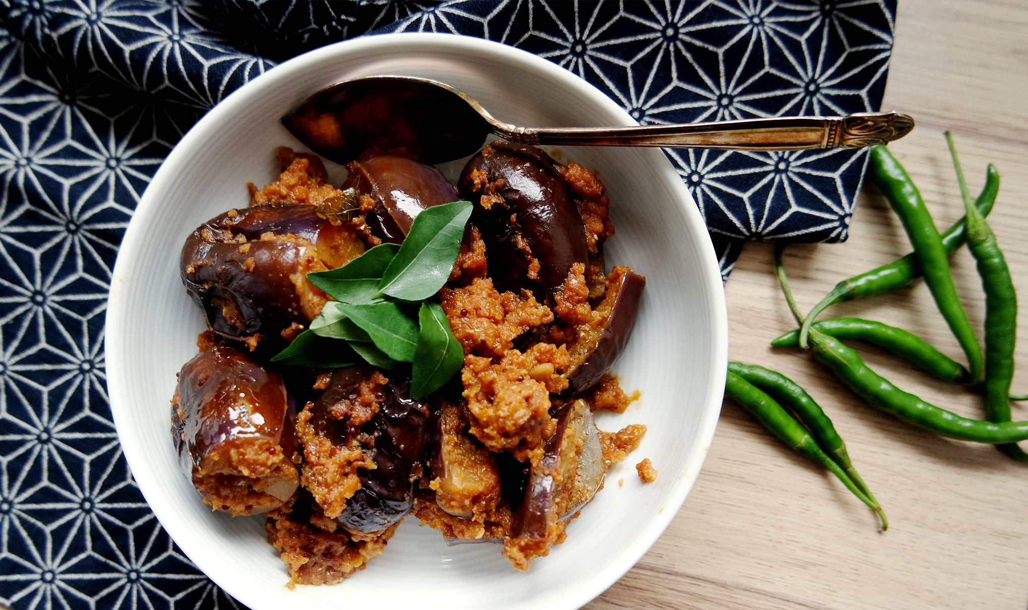 auberginesStuffed with spices in an Indian vegetarian recipe in a white ceramic bowl on a Japanese-patterned fabric