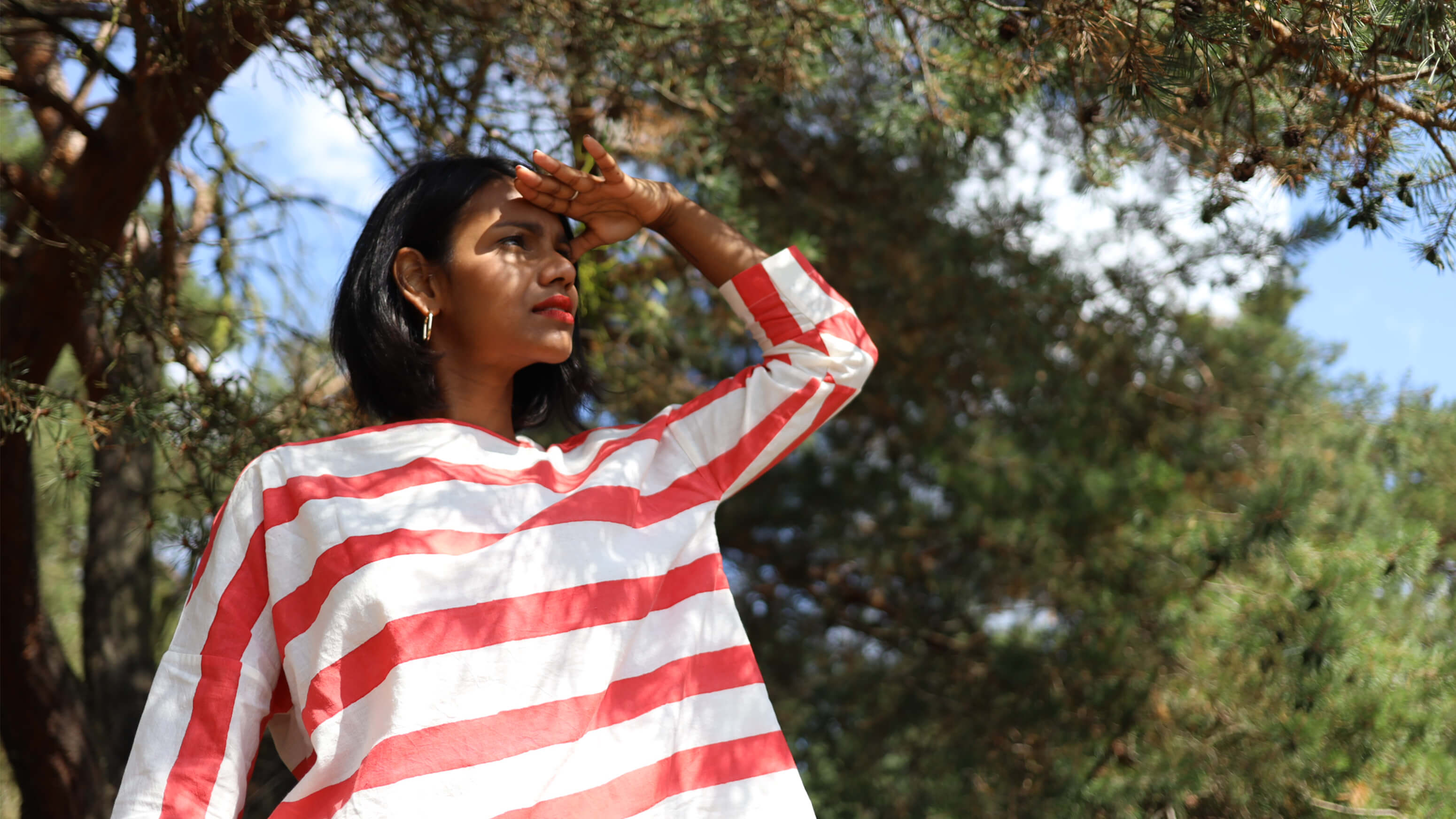 female model wearing red white striped cotton top with a green background and hand raised to shield from the sun