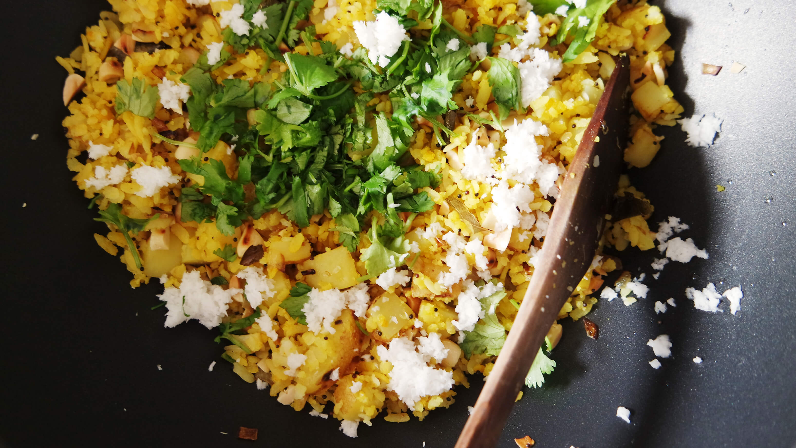 closeup of poha or beaten rice flakes with coriander leaves, fresh coconut and peanuts in a black wok with a wooden cooking spoon