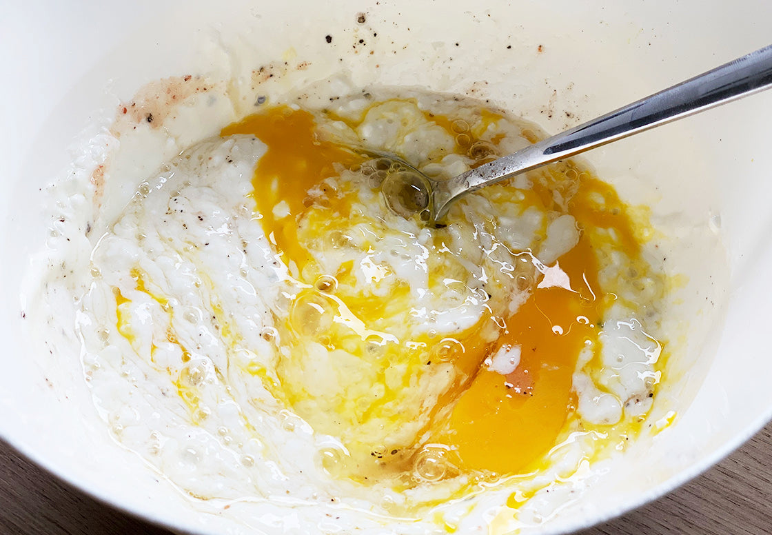 Cottage cheese being mixed with whole organic eggs, yoghurt, salt and pepper in the process of making a pumpkin spinach tarte