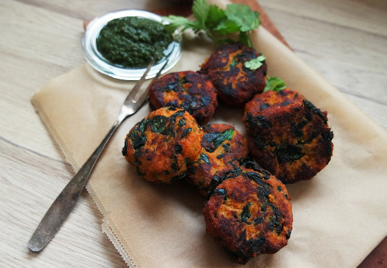 closeup of sweet potato and spinach cutlets spiced with turmeric and cumin, lying on a piece of baking paper next to green chutney