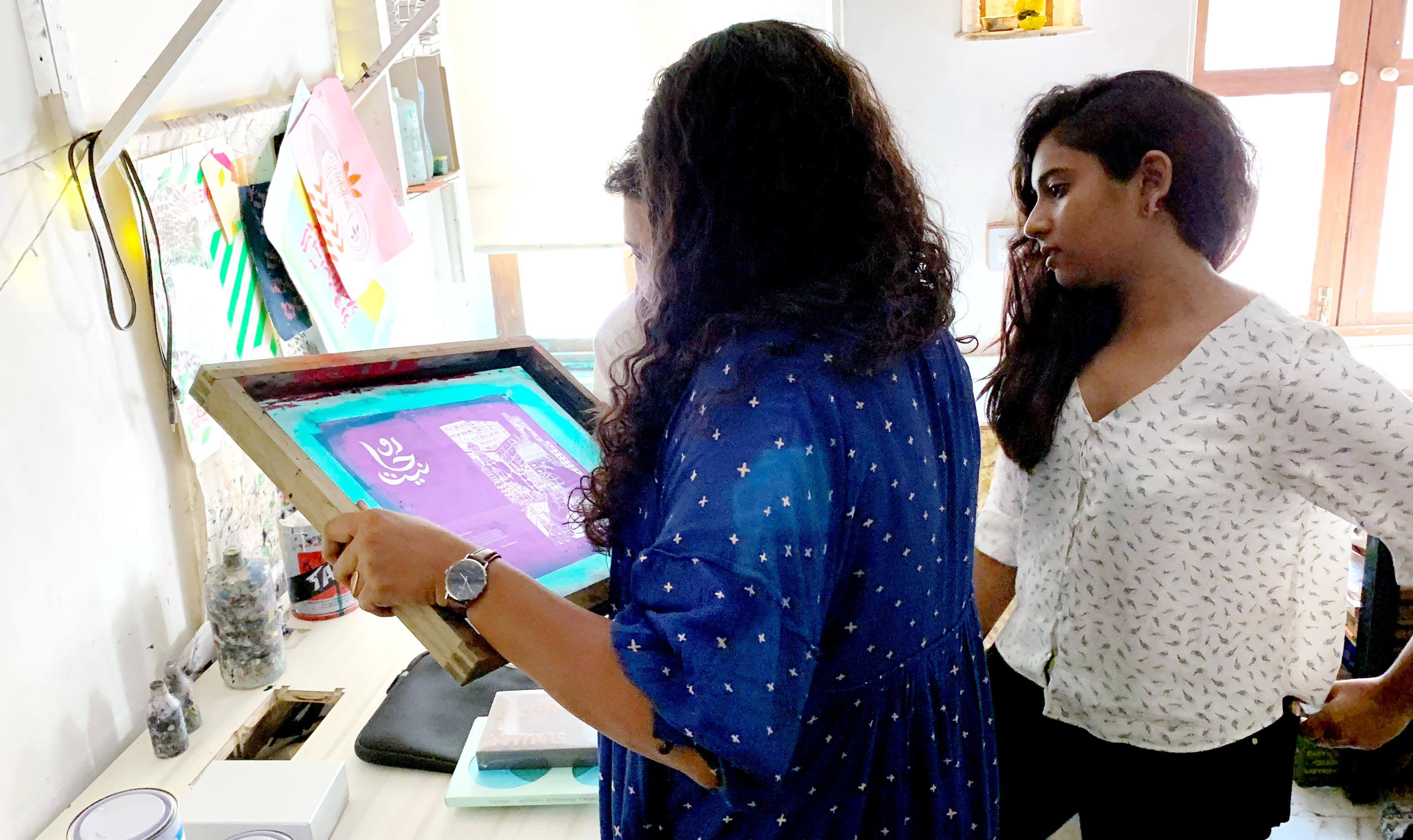 Profile of two ladies with long black wearing  blue and white blouses looking at a developed screen in a printing studio