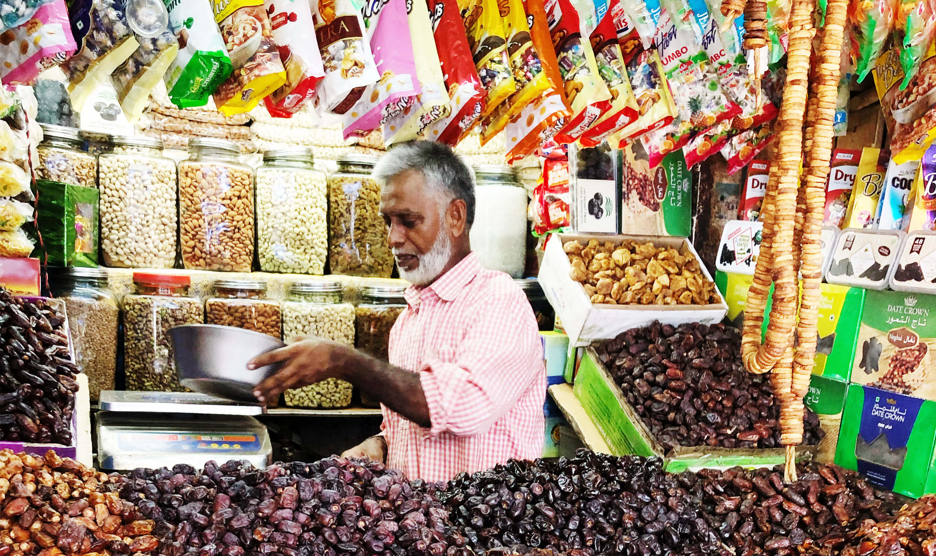 An Indian male vendor in a pink shirt selling dried fruits and other dry goods in his store in Mumbai