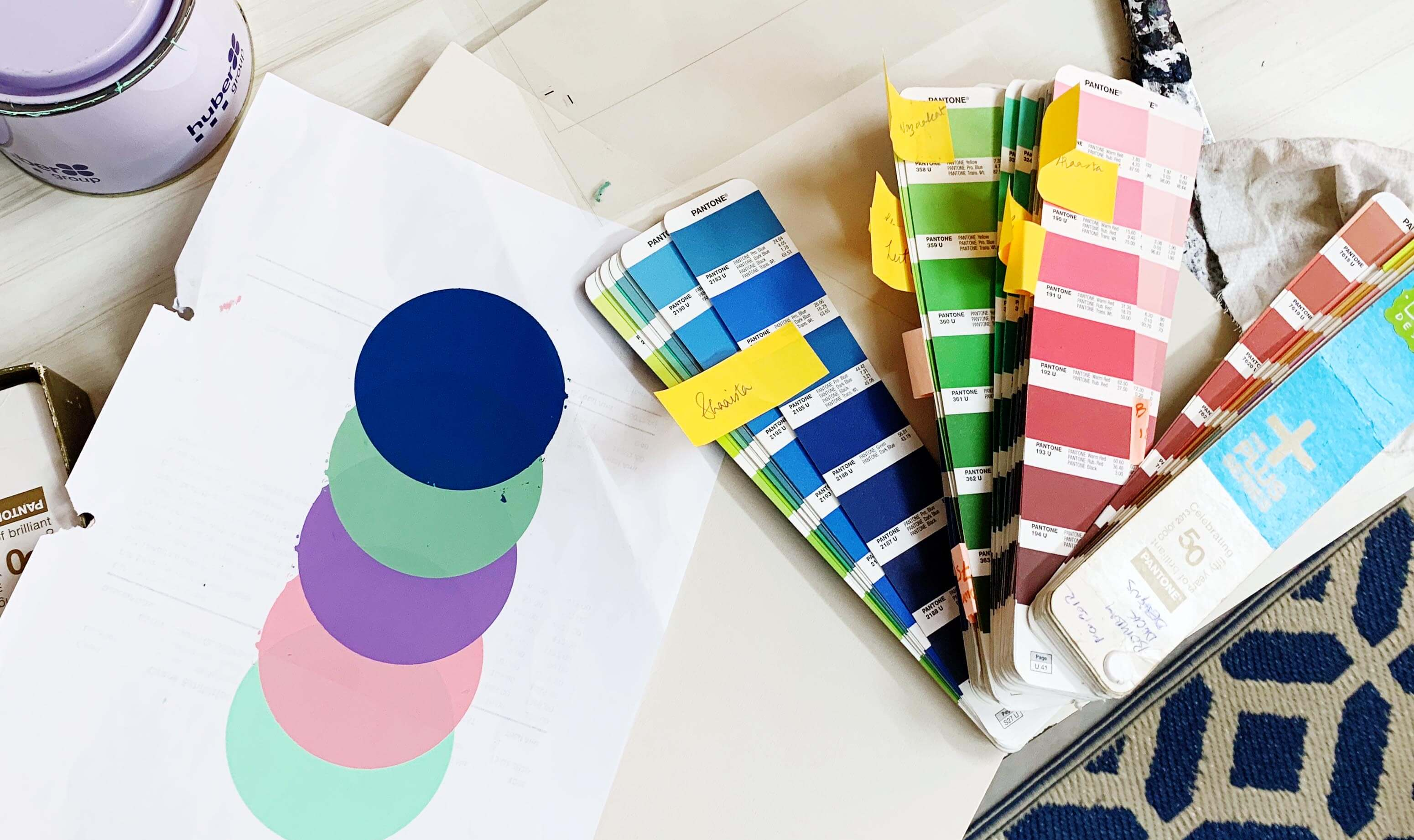Pantone swatch cards lying on a white table next to a paper with five coloured circles printed on it