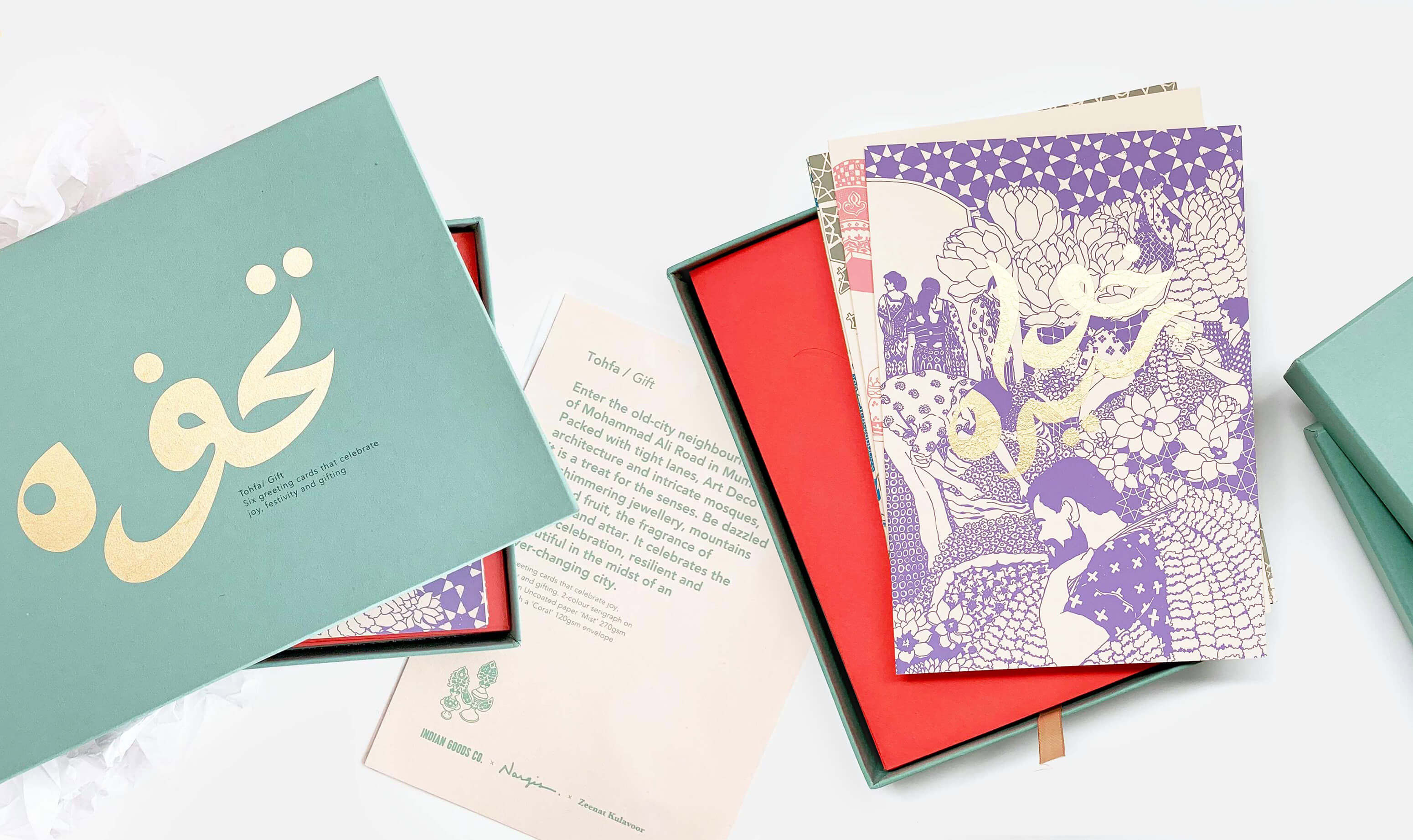 Green box and violet greeting card with screen printed image of flowers and gold Urdu calligraphy on a white table with orange envelope