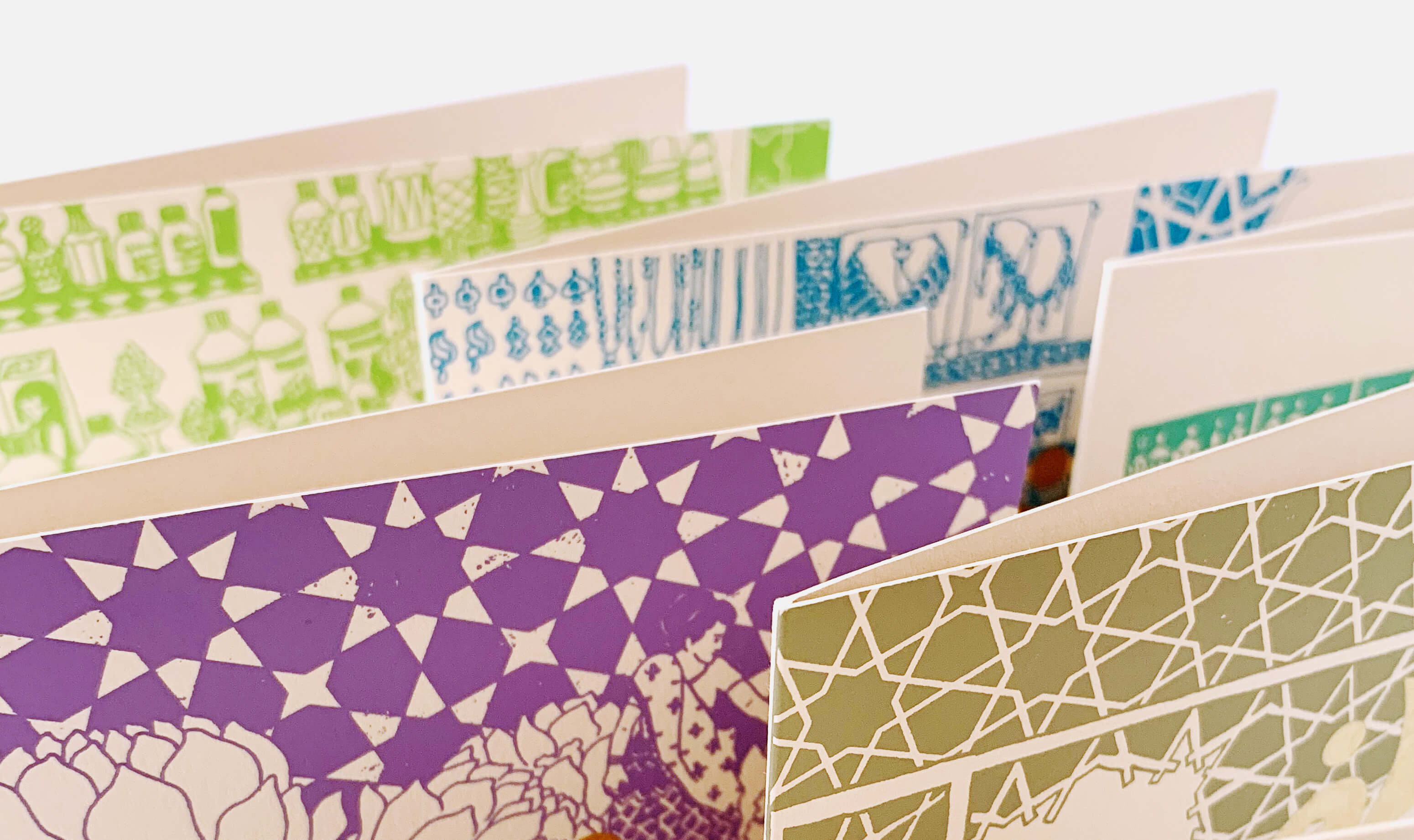 Multiple greeting cards viewed from top in different pastels shades and gold Urdu calligraphy