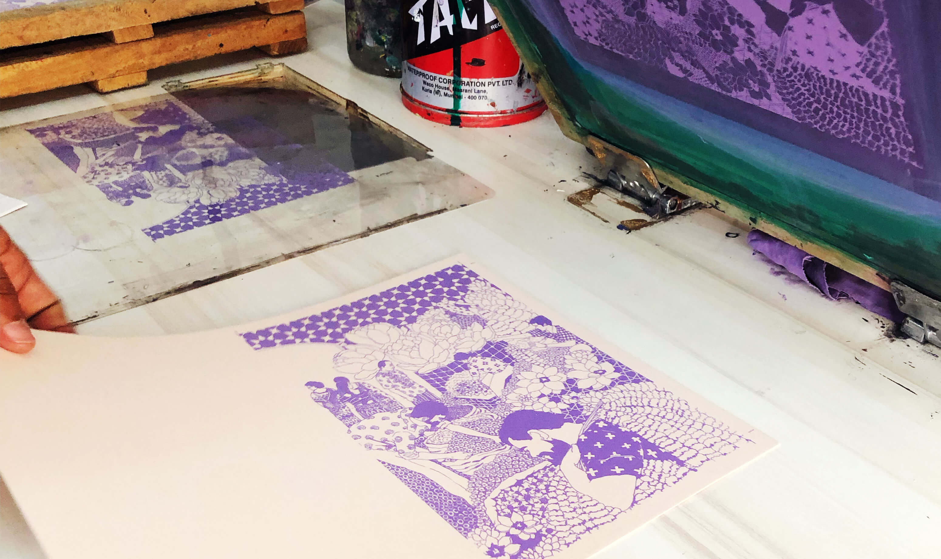 Paper with purple print lying on a white table in a screen print studio with tools lying around