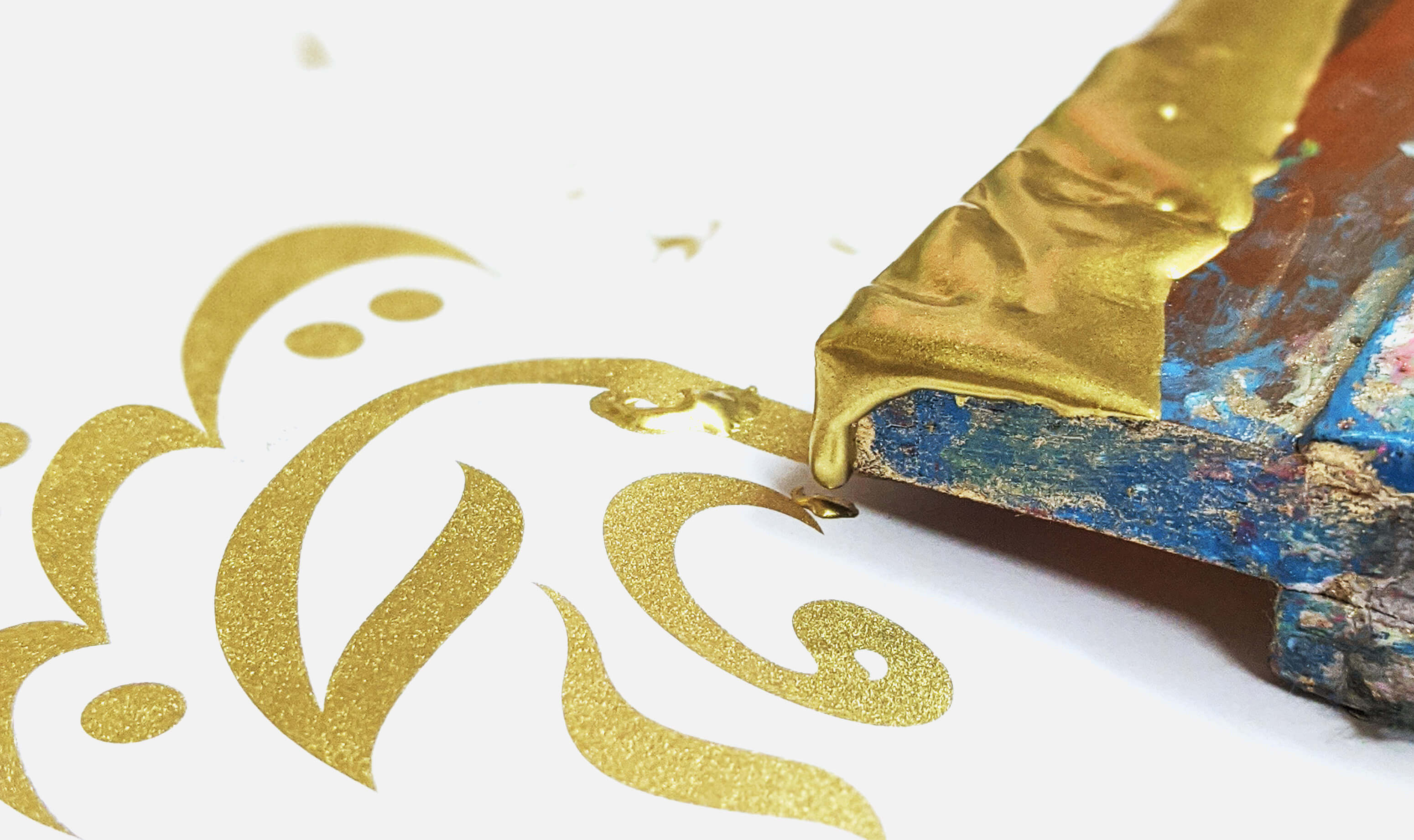 Close up of gold Urdu calligraphy on white paper with a screen printing squeeze lying next to it