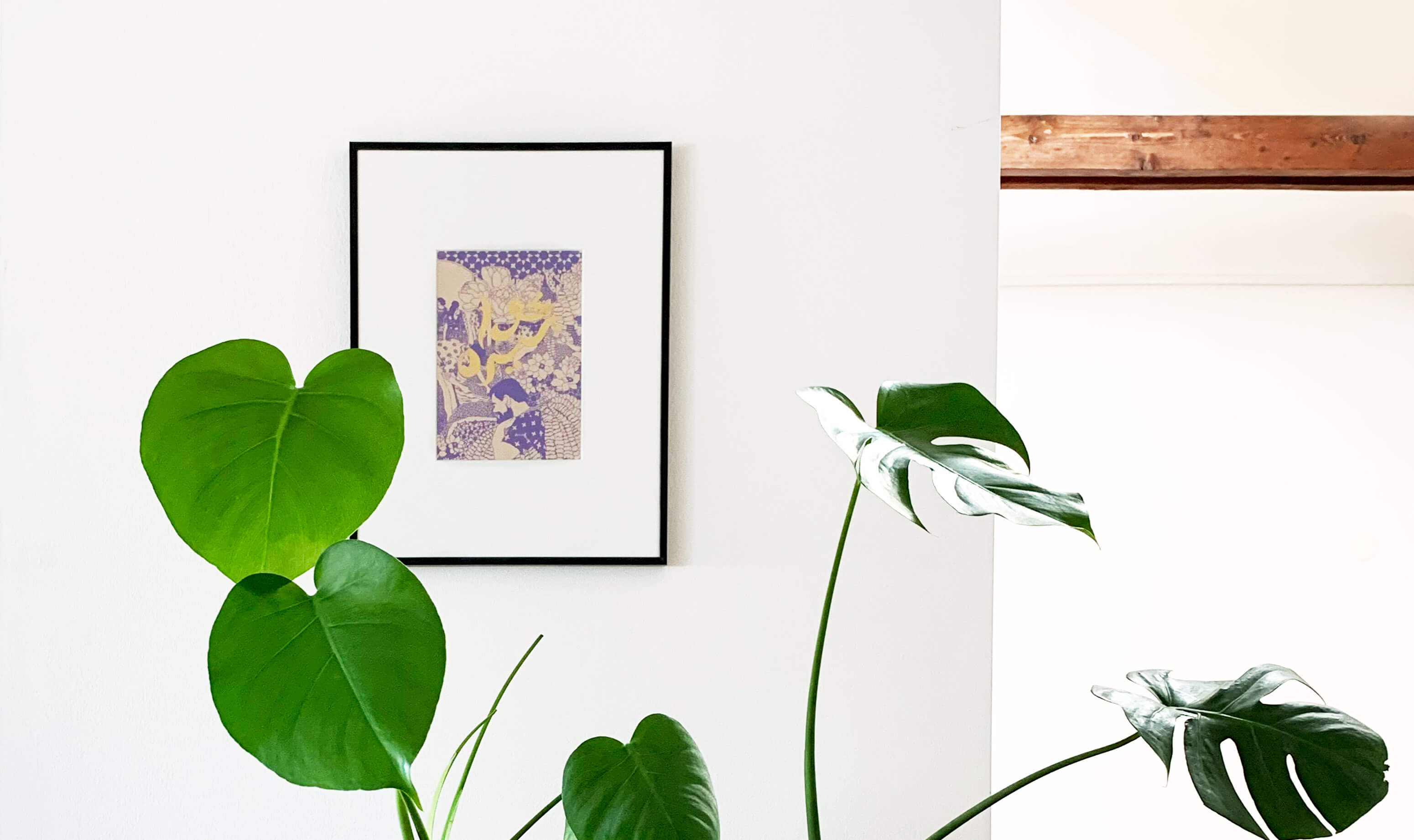 Framed art print with white mask and thin back frame on a white wall with a green plant in front of it