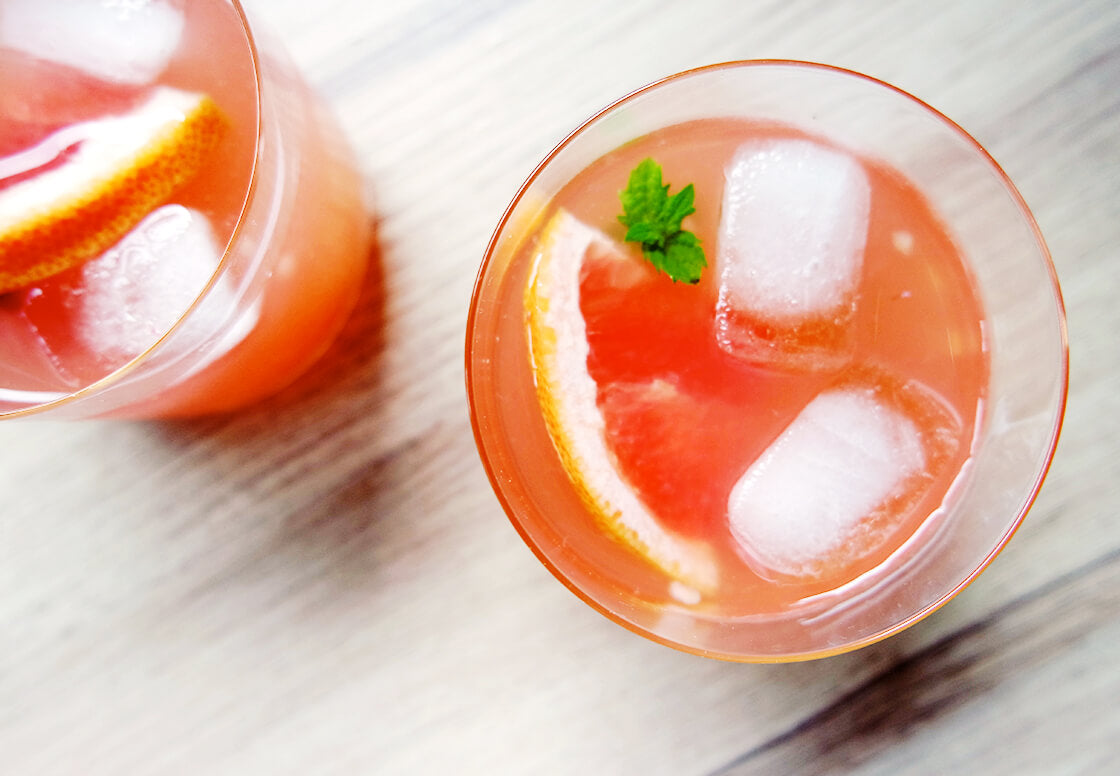 closeup of two glasses with pink lemonade made from grapefruit and orange juice, mixed with raspberries and cardamom sugar, garnished with grapefruit slices