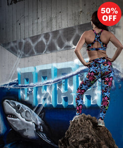 Woman wearing star print fitness wear leggings and racer back bra top by a graffiti shark wall