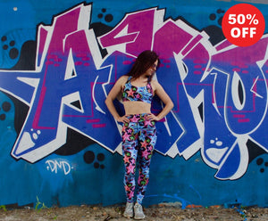 Woman posing in star print fitness wear leggings and bra top by a graffiti wall