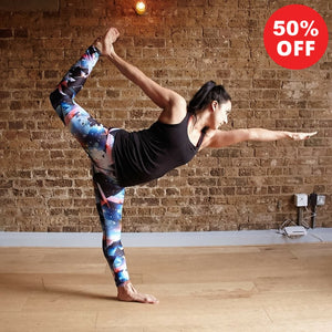 Woman in yoga pose wearing patterned leggings from Flip the Dog against a brick wall backdrop