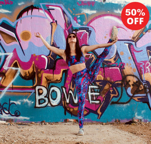 Woman by graffiti wall wearing pink patterned fitness wear leggings and bra top by Flip the Dog