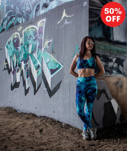 Woman wearing turquoise marble pattern fitness wear leggings and bra top