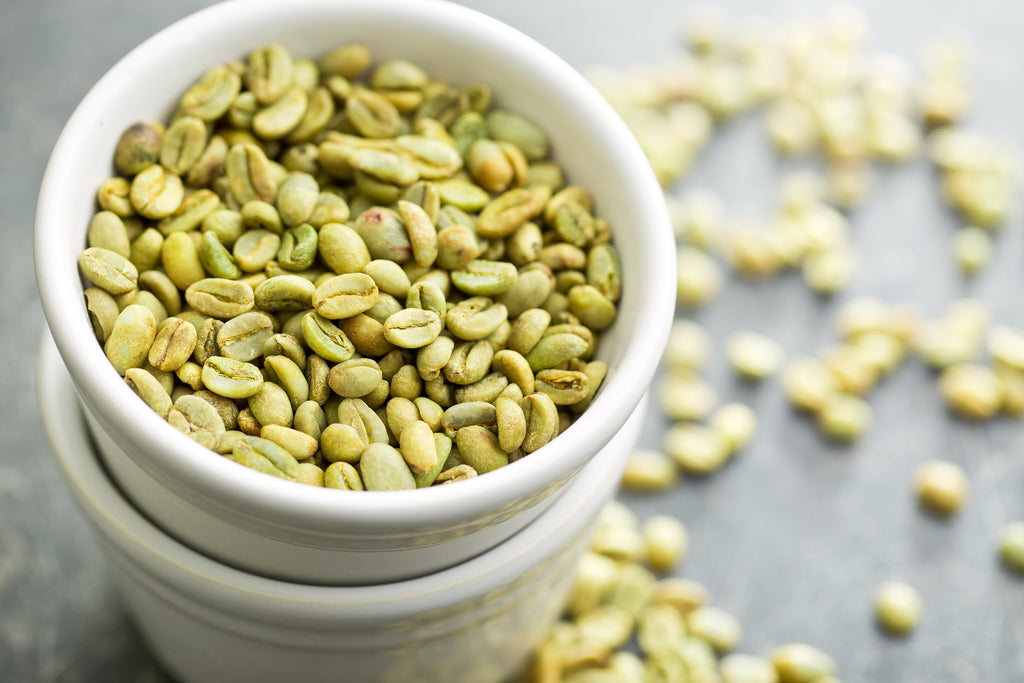 Green coffee beans in a bowl.