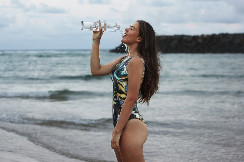 Woman in bathing suit drinking water at the beach