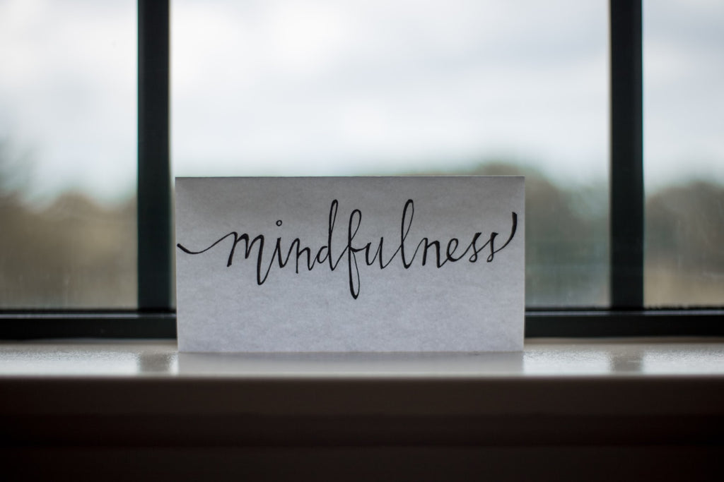 Mindfulness in script on a piece of paper in front of a window