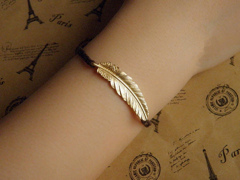 gold tone feather bracelet with brown wax cord