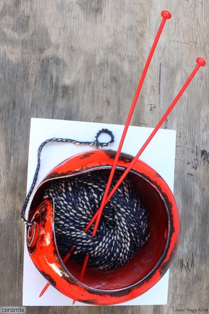 Add your wool and knitting needles to your Dynamic Red Yarn Bowl by Margaret Melville Hugo of Ceramix and start knitting.