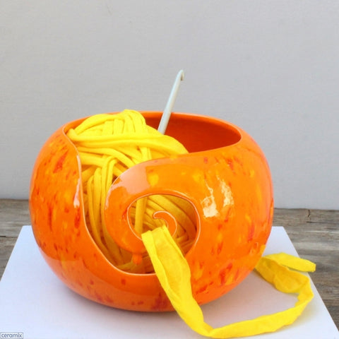 Dazzling Orange Yarn Bowl being used with a crochet hook and yellow yan. Handmade by Margaret Melville Hugo at Ceramix in South Africa