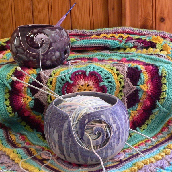 Sugilite Purple Large Round Yarn Bowl and Paradiso Purple Small Round Yarn Bowl shown on a crocheted blanket Handmade by Margaret Melville Hugo with speciality glazes and African clay at Ceramix